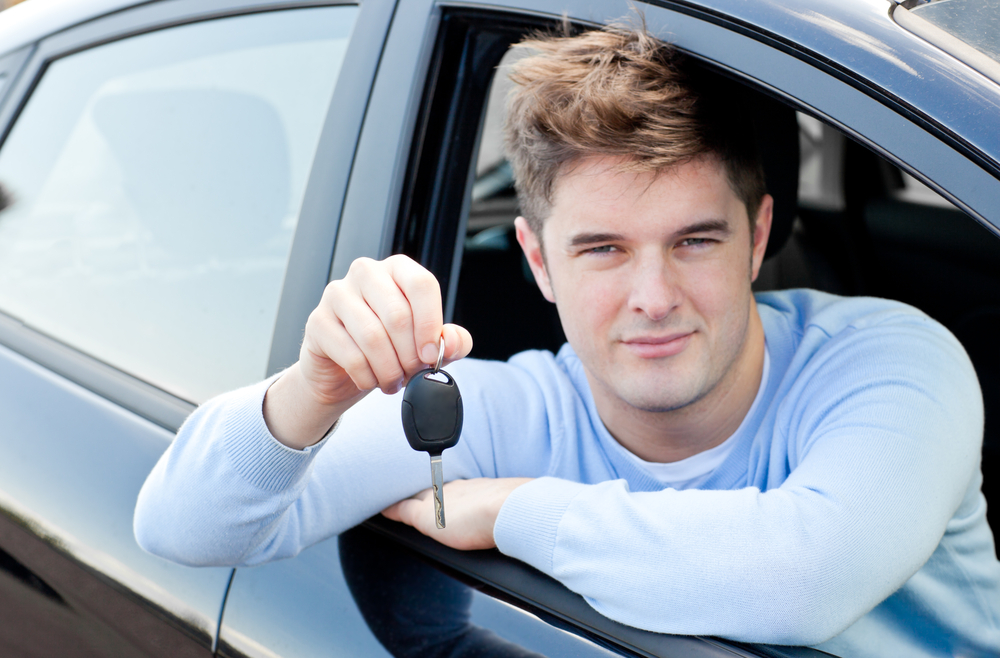 Charming young man holding a car sitting in his car smiling at the camera