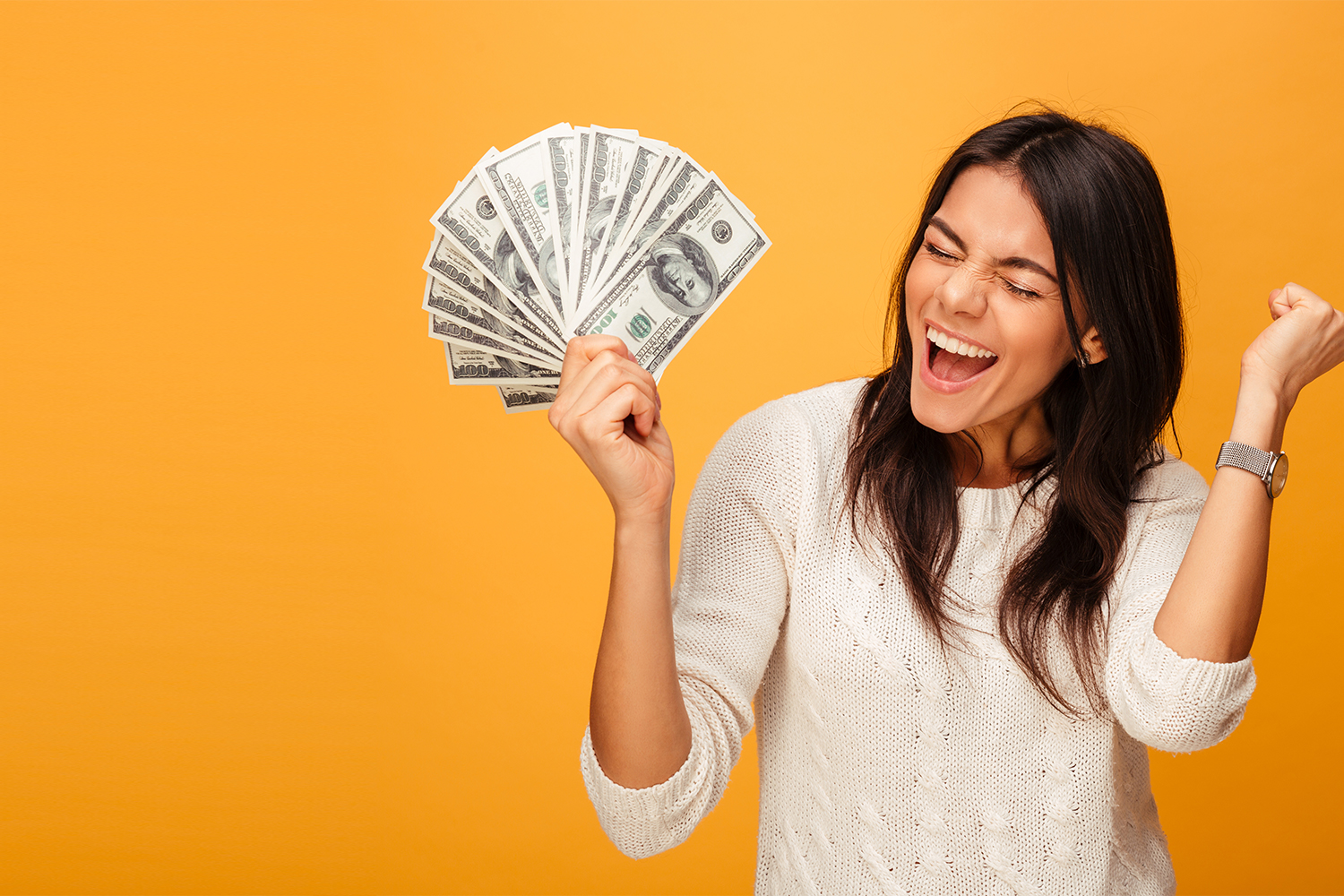shutterstock_1038717511 Portrait of a cheerful young woman holding money banknotes and celebrating isolated over yellow background right